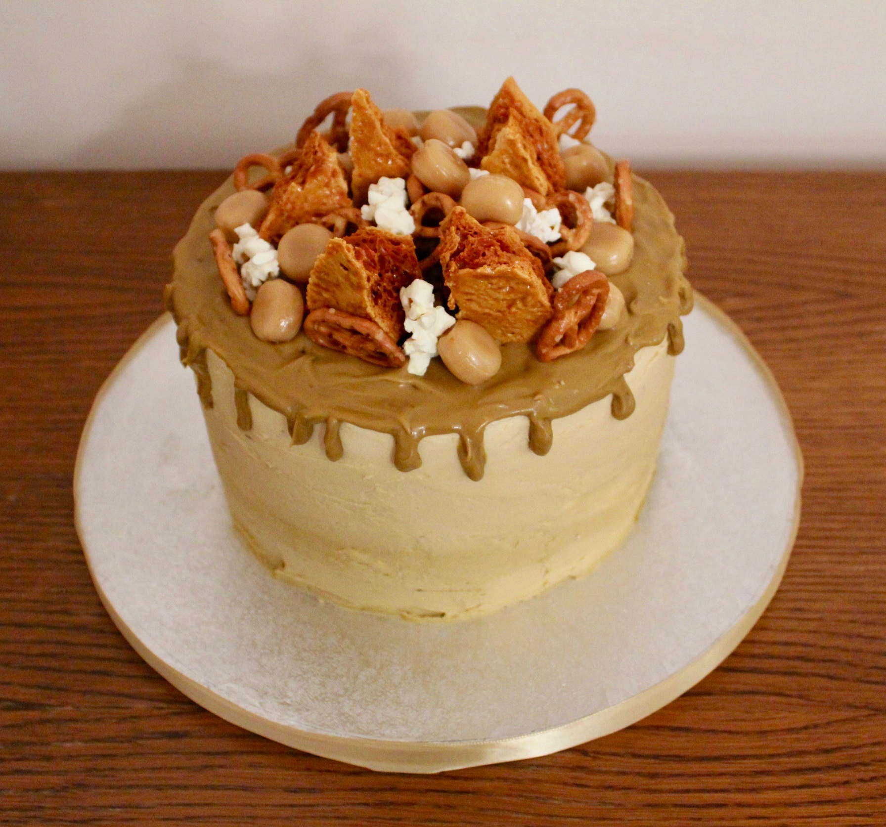 Caramel galore drip cake with honeycomb, popcorn, toffee and pretzels